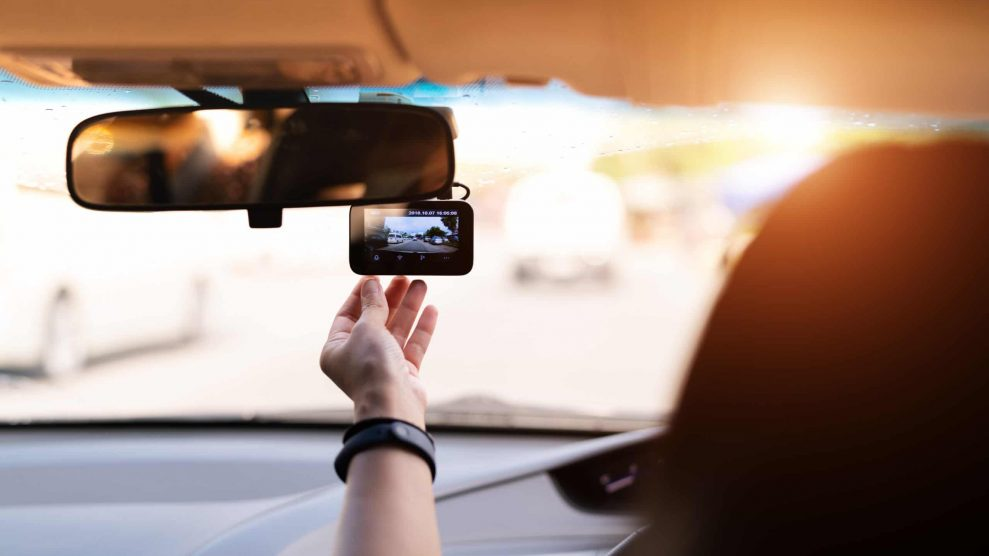 Front camera car recorder, woman set video recorder next to a rear view mirror